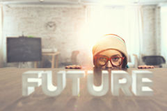 Hipster girl looking from under table . Mixed media Royalty Free Stock Image