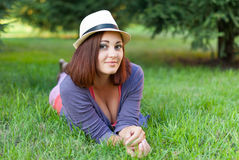 Hipster girl lying in the green grass. Stock Image