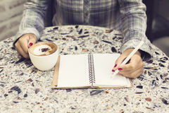Hipster girl making notes in a diary and drinking coffee Royalty Free Stock Photography