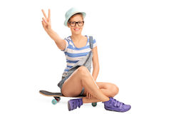 Hipster girl making a peace sign. Studio shot of a hipster girl making a peace hand gesture seated on a skateboard isolated on white background Stock Photo