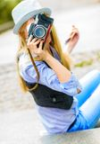 Hipster girl making photo with retro camera Royalty Free Stock Image
