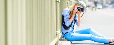 Hipster girl making photo with retro camera while sitting on cit Stock Image
