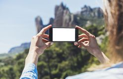 Hipster girl making photo on smartphone mobile closeup, view tourist hands using gadget phone in travel on background mountains royalty free stock image