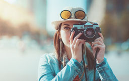 Hipster girl making picture with retro camera, focus on camera Royalty Free Stock Photos