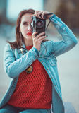 Hipster girl making picture with retro camera. Focus on camera Stock Photos