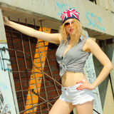 Hipster girl. Modern sexy hipster girl  in shorts and a hat with a picture of the British flag posing on a background of an abandoned building Royalty Free Stock Photos