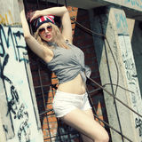 Hipster girl. Modern sexy hipster girl  in shorts and a hat with a picture of the British flag posing on a background of an abandoned building Royalty Free Stock Images