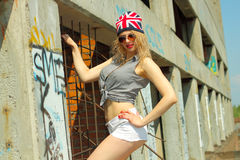 Hipster girl. Modern sexy hipster girl  in shorts and a hat with a picture of the British flag posing on a background of an abandoned building Stock Image