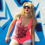 Hipster girl near graffiti. Modern fashion sexy girl in sunglasses posing near a blue wall graffiti Royalty Free Stock Photography