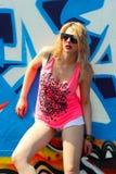 Hipster girl near graffiti. Modern fashion sexy girl in sunglasses posing near a blue wall graffiti Stock Images