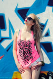 Hipster girl near graffiti. Modern fashion sexy girl in sunglasses posing near a blue wall graffiti Stock Photo