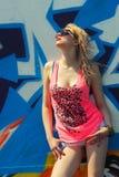 Hipster girl near graffiti. Modern fashion sexy girl in sunglasses posing near a blue wall graffiti Stock Photography