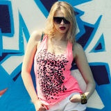 Hipster girl near graffiti. Modern fashion sexy girl in sunglasses posing near a blue wall graffiti Royalty Free Stock Photos