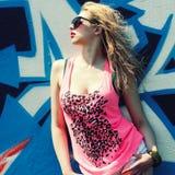 Hipster girl near graffiti. Modern fashion sexy girl in sunglasses posing near a blue wall graffiti Stock Image