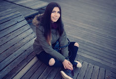 Hipster girl in parka coat sitting outdoors Stock Images