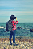 Hipster girl photographing sea Stock Photography