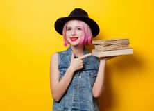 Hipster girl with pink hairstyle with books. Portrait of young style hipster girl with pink hairstyle with books on yellow background Royalty Free Stock Photo