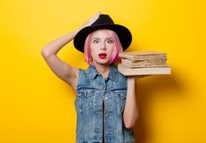 Hipster girl with pink hairstyle with books. Portrait of young style hipster girl with pink hairstyle with books on yellow background Stock Photos