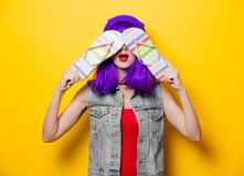 Hipster girl with pink hairstyle with flip flops. Portrait of young style hipster girl with purple hairstyle with flip flops shoes on yellow background Royalty Free Stock Photo