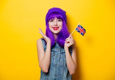 Hipster girl with pink hairstyle with flip flops. Portrait of young style hipster girl with purple hairstyle with flip flops shoes on yellow background Royalty Free Stock Photography
