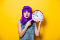 Hipster girl with pink hairstyle with flip flops. Portrait of young style hipster girl with purple hairstyle with flip flops shoes on yellow background Royalty Free Stock Images