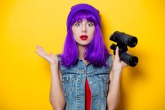 Hipster girl with pink hairstyle with flip flops. Portrait of young style hipster girl with purple hairstyle with flip flops shoes on yellow background Royalty Free Stock Photos