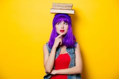 Hipster girl with pink hairstyle with flip flops. Portrait of young style hipster girl with purple hairstyle with flip flops shoes on yellow background Stock Photo