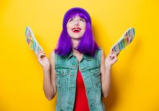 Hipster girl with pink hairstyle with flip flops. Portrait of young style hipster girl with purple hairstyle with flip flops shoes on yellow background Stock Images