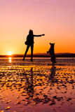 Hipster girl playing with dog at a beach during sunset, silhouettes Royalty Free Stock Images