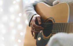 Hipster girl playing guitar in a homelike atmosphere, person studying on musical instrument on glow bokeh Christmas illimination stock photo