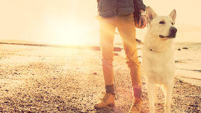 Free Hipster Girl Playing With Dog At A Beach During Sunset, Strong Lens Flare Effect Stock Photo - 54472670