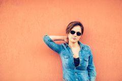 Hipster girl posing, against orange background on city streets. Urban lifestyle of contemporary world Royalty Free Stock Photo