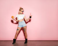 Hipster girl posing with burger and cola. Young hipster tattooed girl in casual clothing and sunglasses posing with burger and cola on pink Stock Images