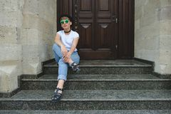 Beautiful young hipster woman posing sitting on stairs royalty free stock photography