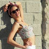 Hipster girl posing. Vintage positive girl in sunglasses enjoying life. On the background of a brick wall. Lifestyle portrait Royalty Free Stock Photos