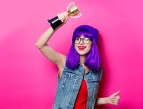 Hipster girl with purple hair with trophy cup. Portrait of young style hipster girl with purple hair with trophy cup on pink background royalty free stock photo