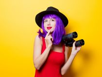 Hipster girl with purple hairstyle and binoculars. Portrait of young style hipster girl with purple hairstyle and binoculars on yellow background Royalty Free Stock Photos