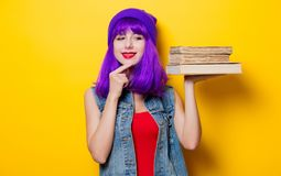 Hipster girl with purple hairstyle with books. Portrait of young style hipster girl with purple hairstyle with books on yellow background Stock Photography