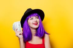 Hipster girl with purple hairstyle with money. Portrait of young style hipster girl with purple hairstyle with money on yellow background Royalty Free Stock Photo