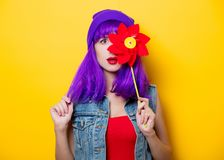 Hipster girl with purple hairstyle with pinwheel. Portrait of young style hipster girl with purple hairstyle with pinwheel on yellow background Stock Photography