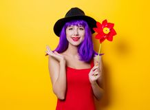 Hipster girl with purple hairstyle with pinwheel. Portrait of young style hipster girl with purple hairstyle with pinwheel on yellow background Royalty Free Stock Image