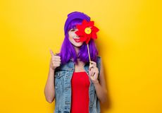 Hipster girl with purple hairstyle with pinwheel. Portrait of young style hipster girl with purple hairstyle with pinwheel on yellow background Royalty Free Stock Images