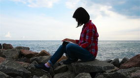 Hipster girl reading a book. Hipster girl sitting on rock and reading a book stock video footage