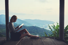 Hipster girl is reading electronic book via digital tablet. Young female freelancer is working in network via touch pad, while is sitting against beautiful view Royalty Free Stock Images