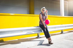 Hipster girl with red balloon posing at parking lot Royalty Free Stock Photos