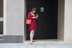 Hipster girl in red dress dressed in cool Londoner style standing near wall Stock Image