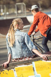 Hipster girl resting at skateboard park while boy riding bicycle Royalty Free Stock Image