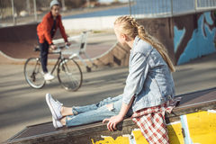 Hipster girl resting at skateboard park while boy riding bicycle Stock Photos