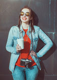 Hipster girl with retro camera and cup of coffee Stock Images