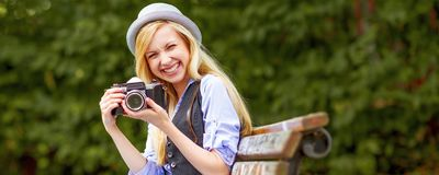 Hipster girl with retro photo camera sitting on bench in Stock Photography